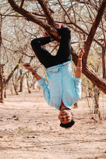 Man hanging from tree on land