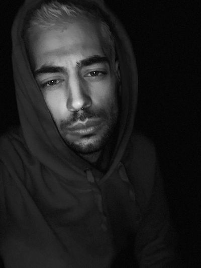 Portrait Of Young Man Wearing Hooded Shirt Against Black Background