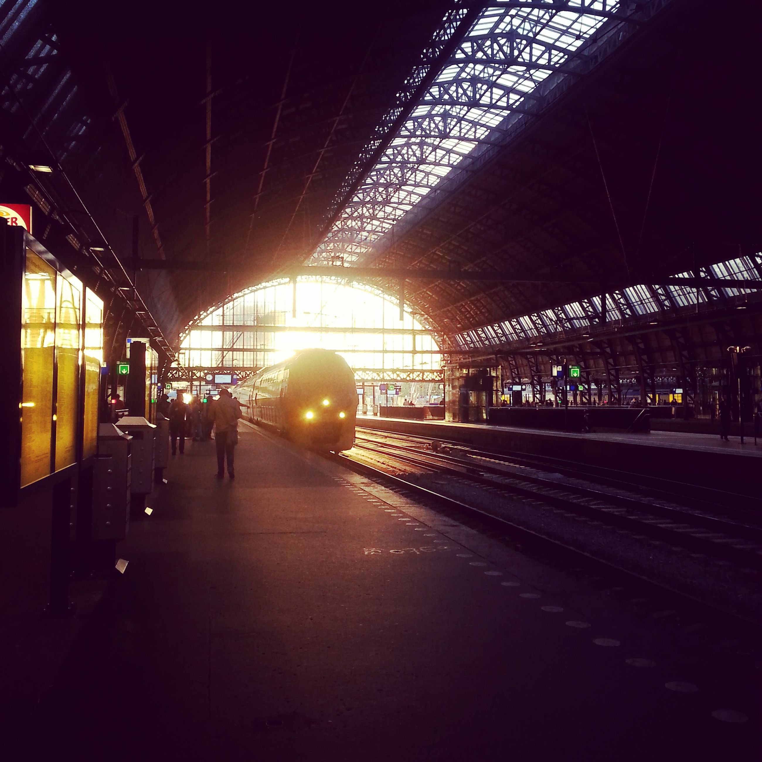 indoors, railroad station, transportation, illuminated, railroad track, railroad station platform, public transportation, rail transportation, built structure, ceiling, architecture, the way forward, incidental people, travel, architectural column, lighting equipment, arch, diminishing perspective, interior