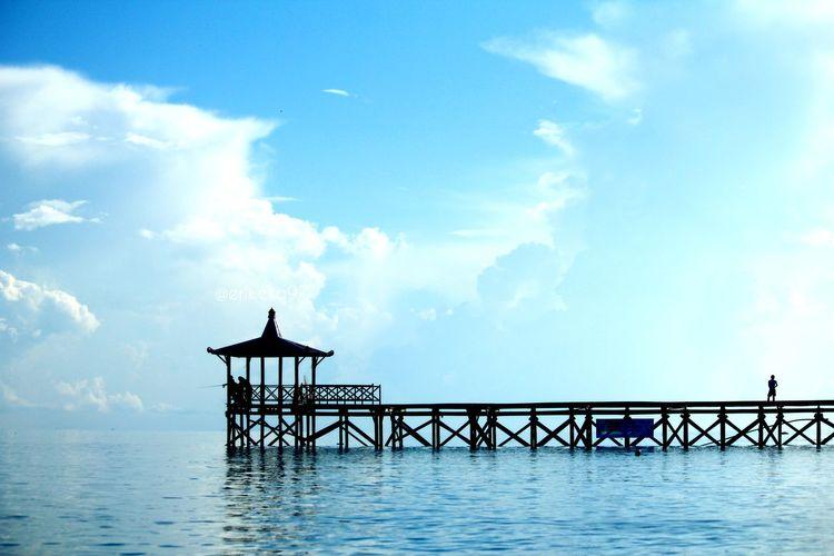 Silhouette pier over sea against blue sky