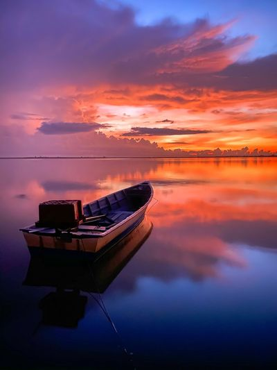 Boat moored on sea against sky during sunset