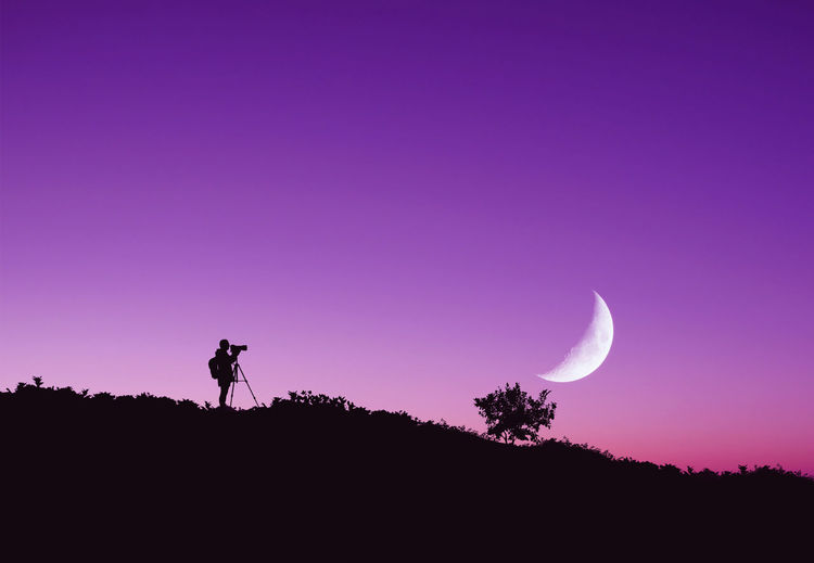 Low angle view of photographer standing on hill against purple sky