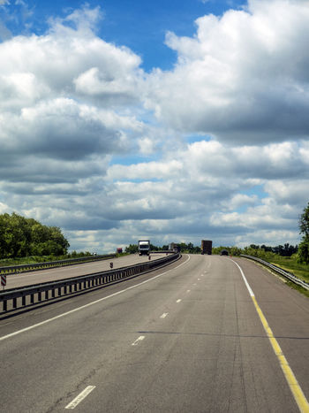 """Highway """"South"""" near Novovoronezh, Russia Architecture Cargo Cloud - Sky Day Dividing Line Highway Industry Mode Of Transport Nature No People Outdoors Road Road Marking Sky South The Way Forward Transportation Tree Truck Wheel"""