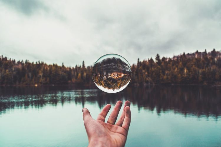 Close-up of hand playing with crystal ball against lake