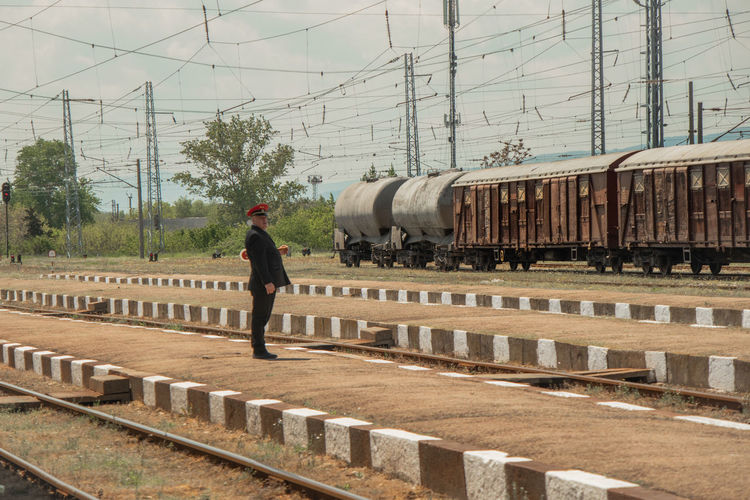 Man standing on railroad track by train