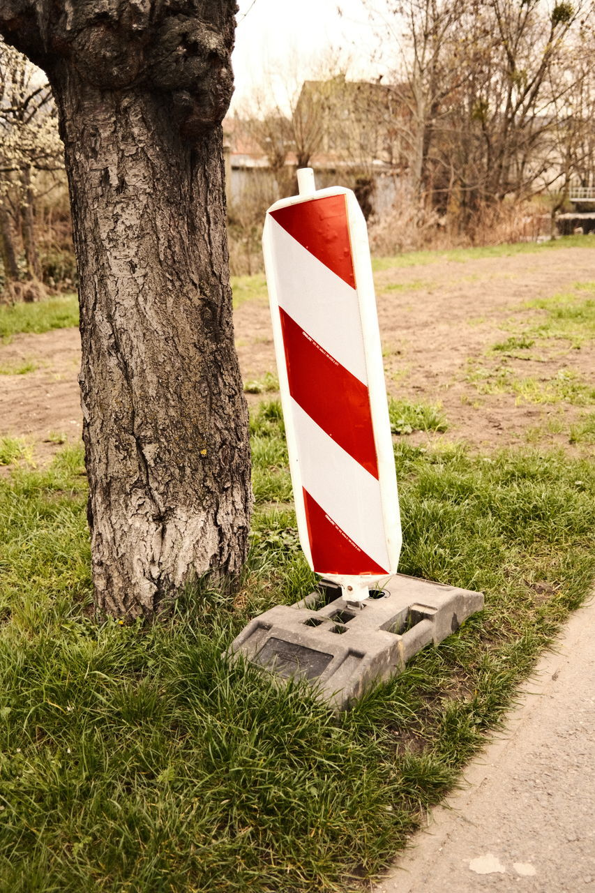 SIGN BOARD ON TREE TRUNK