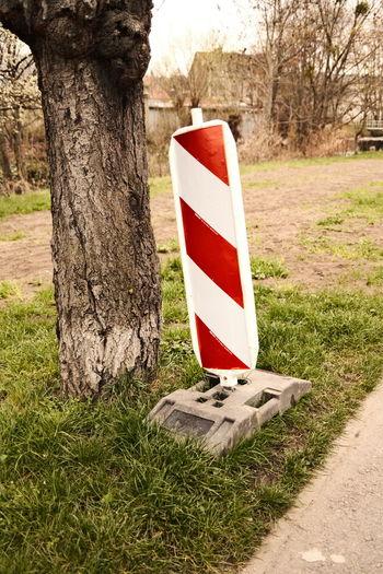Sign board on tree trunk by field