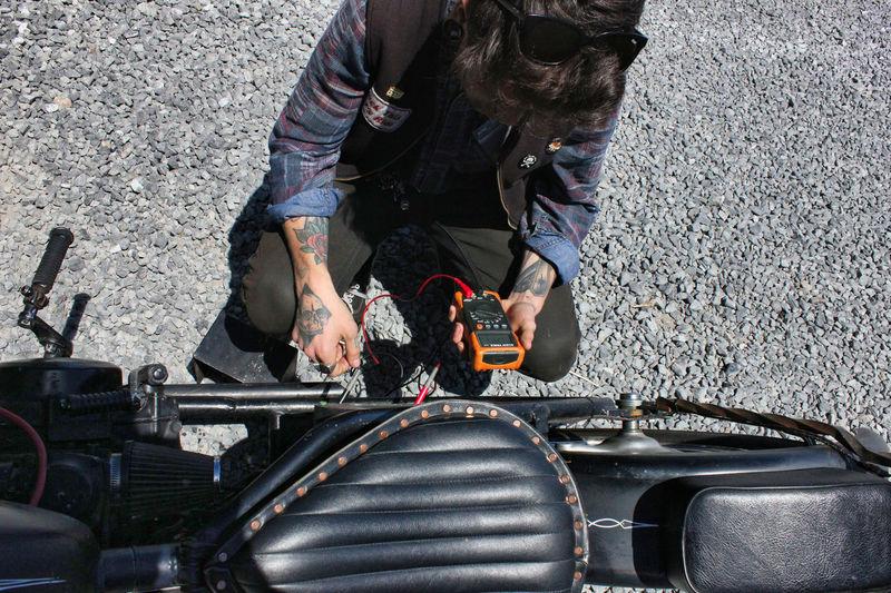 High angle view of man examining motorcycle