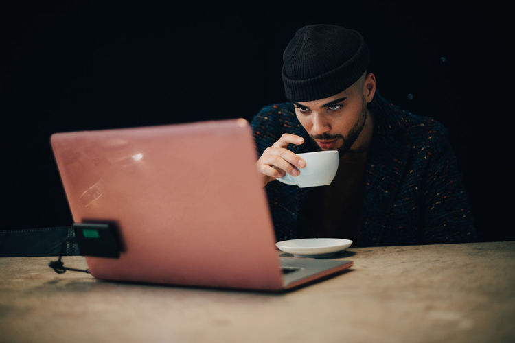 Man drinking coffee cup on table