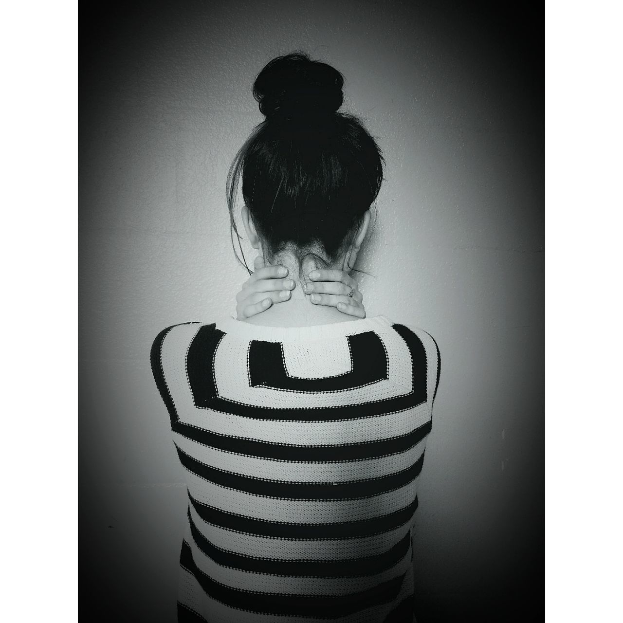 REAR VIEW OF WOMAN STANDING AGAINST GRAY BACKGROUND