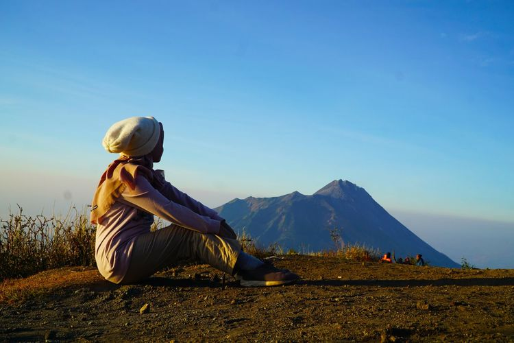 Side view of woman sitting on mountain against sky at sunset