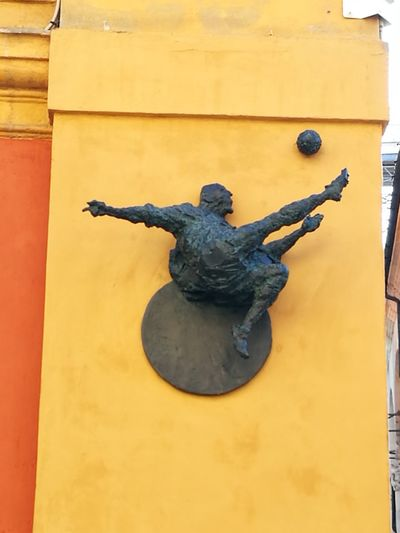 Low angle view of statue against yellow wall