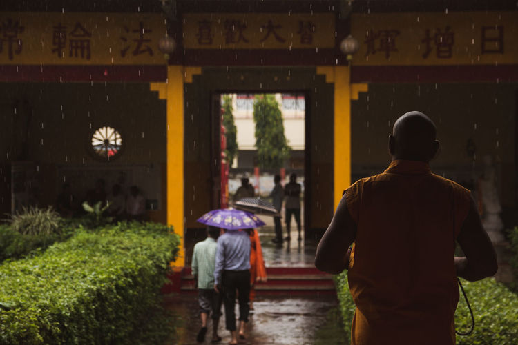 Rear view of people walking on a chinese monastery