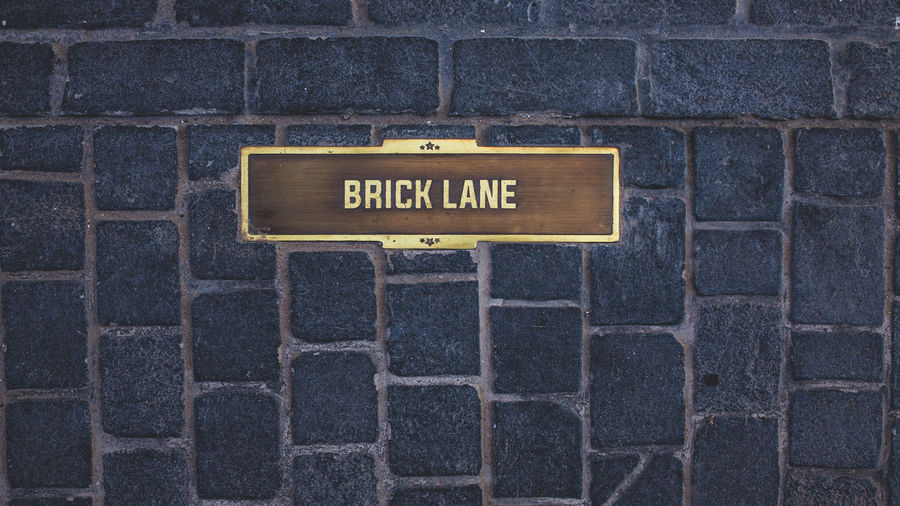 Brick lane Architecture Brick Wall Capital Letter Close-up Communication Day Nameplate No People Outdoors Text Western Script No Parking Sign Information Sign Arrow Sign Directional Sign Building Exterior Brick Building Residential Structure Historic Tall Non-western Script Exterior Office Building Pedestrian Crossing Sign Warning Sign Street Name Sign Single Word Sign Information