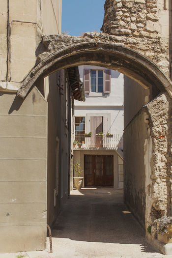 A narrow street at Arles, France Arch Architecture Building Exterior Built Structure City Day House Narrow No People Outdoors Residential Building Residential District Residential Structure Sky The Way Forward Tourism Travel Destinations