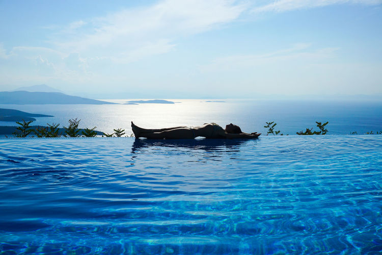 Woman lying amidst swimming pool and sea