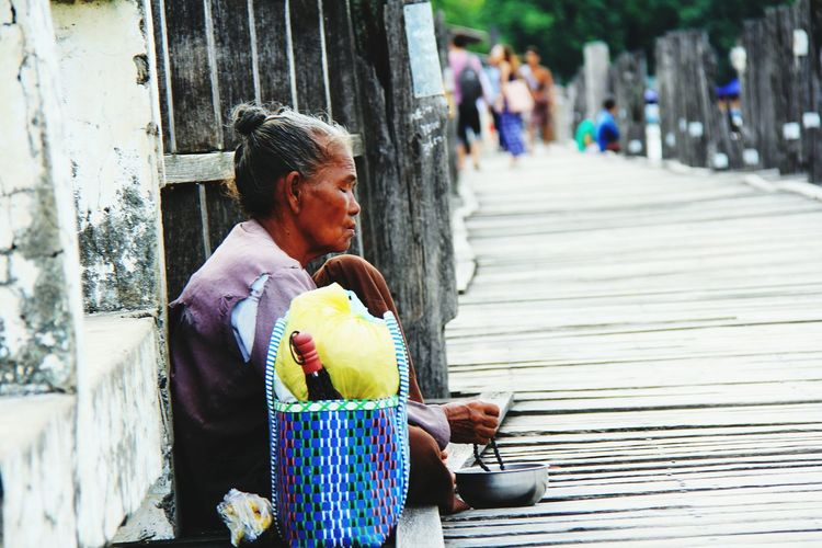 Side view of mature woman begging on pier