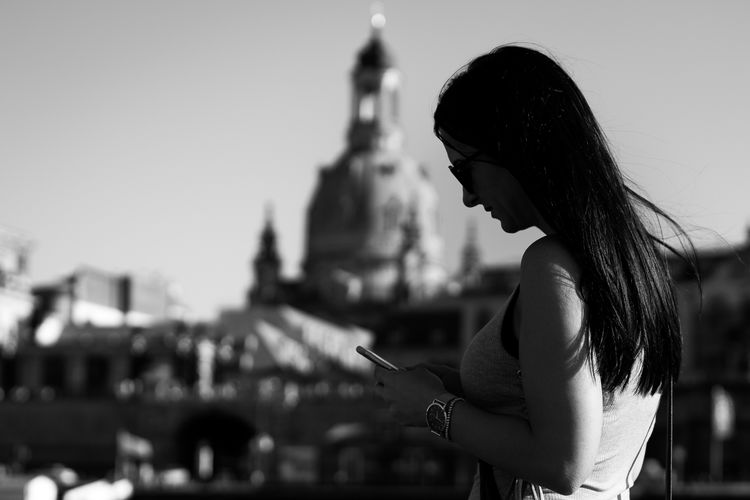 Side view of woman using mobile phone while standing against clear sky in city