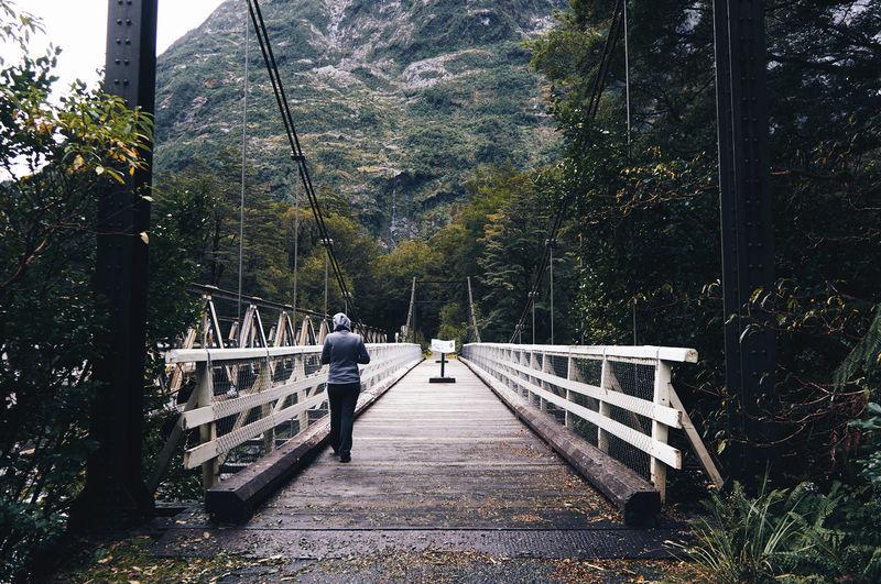 Rear View Of Person Walking On Footbridge Leading Towards Mountain
