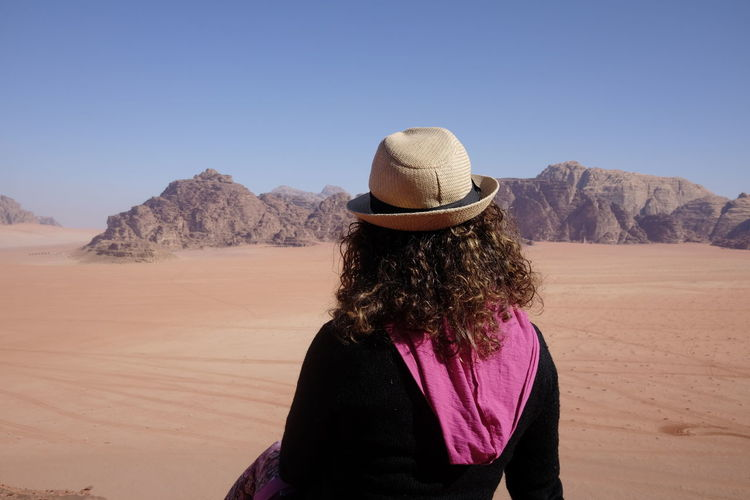 Rear view of woman standing in desert against sky
