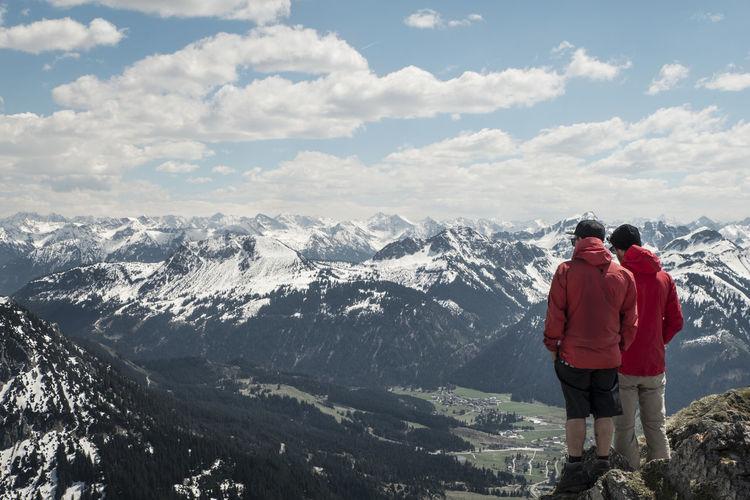 Rear view of men against european alps