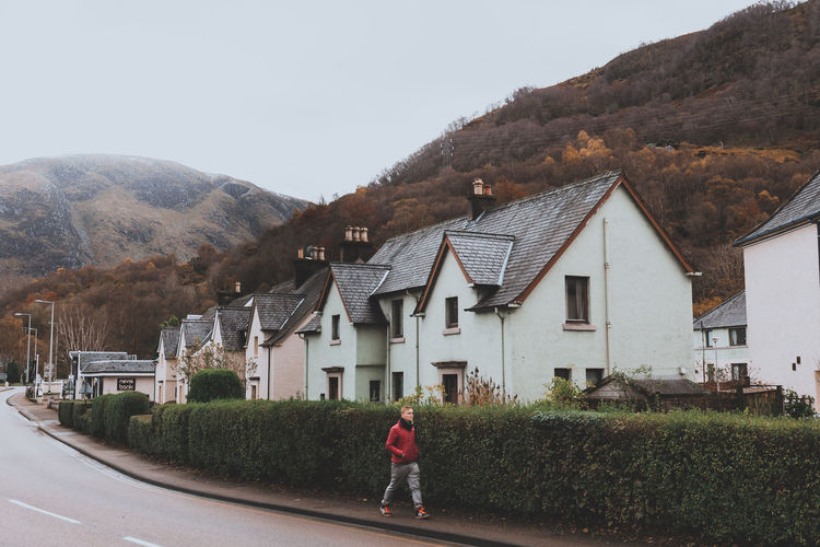 Village people. | IG: @Lostboymemoirs Architecture Building Exterior Mountain Building Built Structure Sky One Person Day Road House Plant Nature Tree Real People Transportation Residential District Standing Rear View Full Length Outdoors Streetphotography Street Photography City Life Peope Peopel Photography people and places The Week on EyeEm Best EyeEm Shot Scotland Hillside Village The Art Of Street Photography