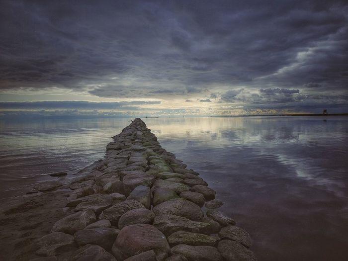 Rocks on sea against sky during sunset