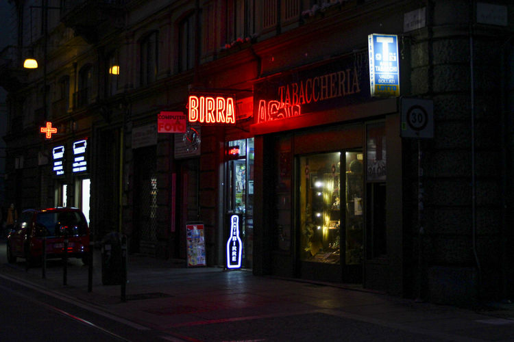 Illuminated sign on street by building at night
