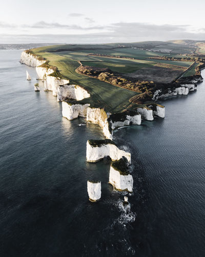 Aerial view of cliff by sea against sky during winter