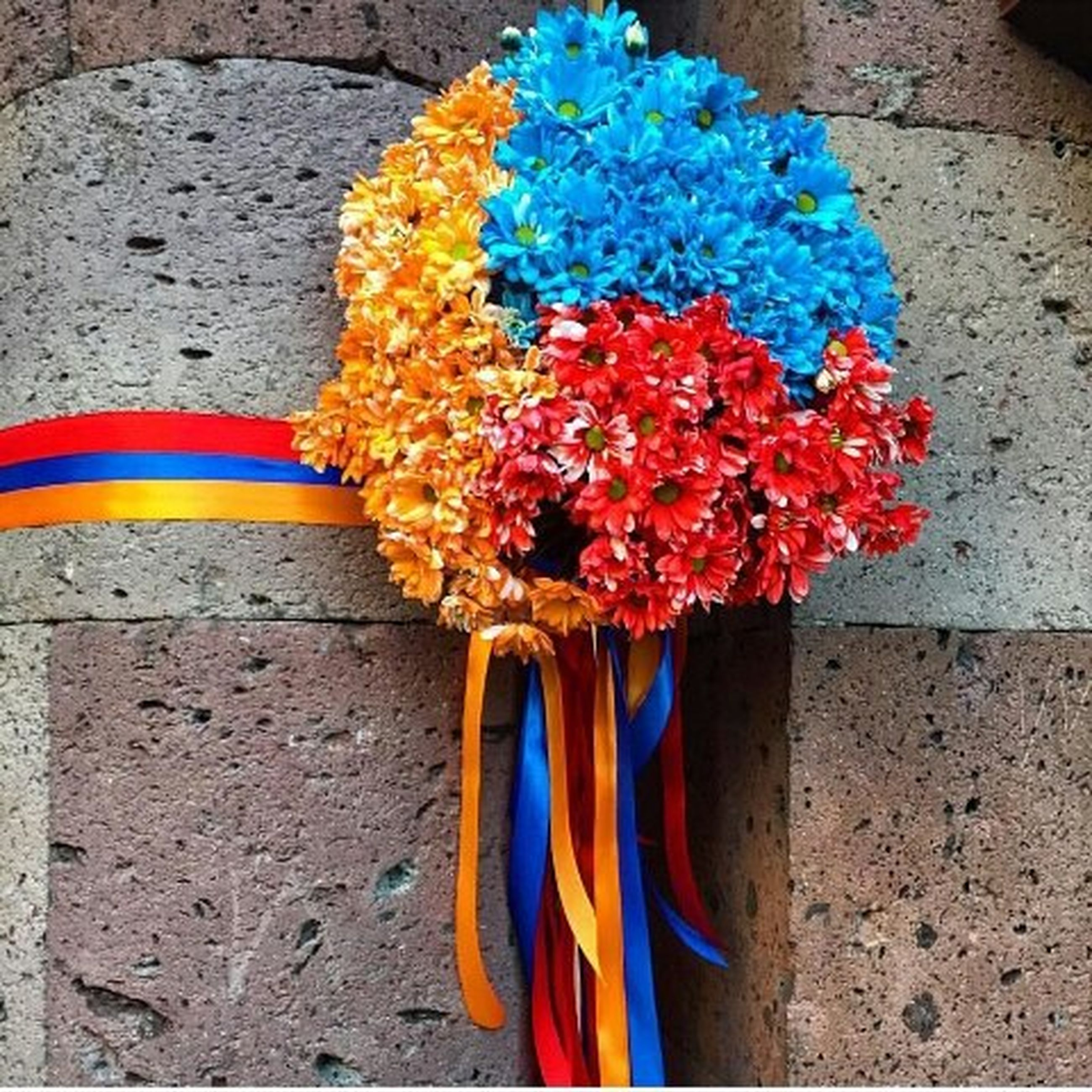 multi colored, flower, colorful, high angle view, blue, variation, yellow, close-up, street, red, wall - building feature, day, outdoors, no people, petal, striped, art and craft, vibrant color, fragility, art