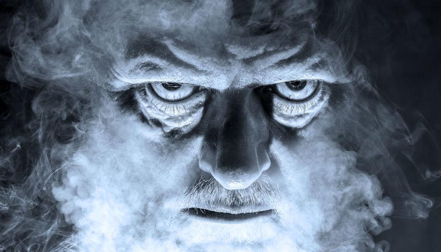 Close-up portrait of spooky man amidst smoke