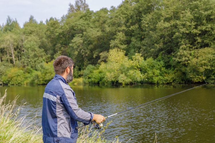 Man fishing in lake against trees
