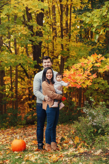Full length of family standing in forest during autumn