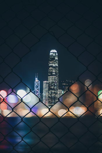 EyeEm Selects Chainlink Fence Skyscraper Night Illuminated Building Exterior City Architecture Cityscape Protection Downtown District No People Urban Skyline Outdoors Sky Close-up Street Architecture People Sea Water Men City Nightlife Arts Culture And Entertainment