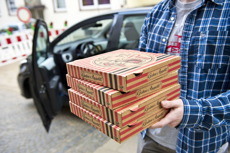 Ein Fahrer eines Pizzataxi liefert Pizza Fast Food Lieferdienst Pizza Time Pizzakarton Car Food Delivery Human Hand One Man Only One Person Pizza Pizza Taxi Pizzataxi