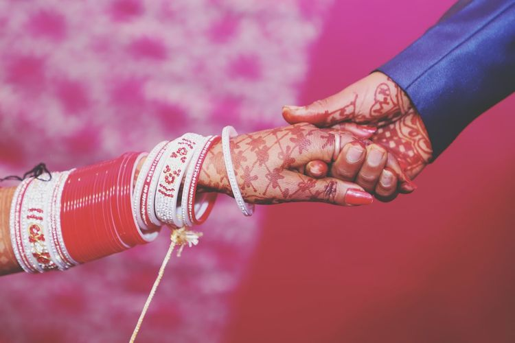 Cropped image of bride and groom holding hands during wedding