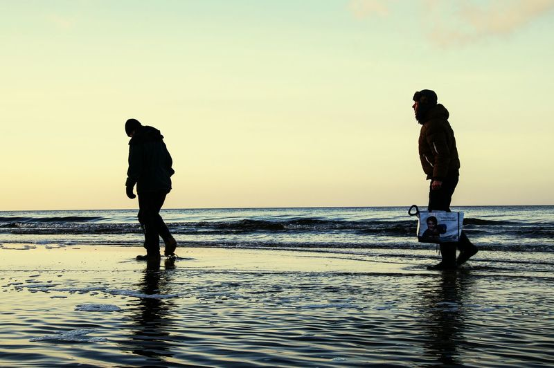 Baltic Sea Go Shopping Walking On Water Winter At The Beach Windy Cold 2 Man Walking Cold Weather People On The Way Let's Go. Together.