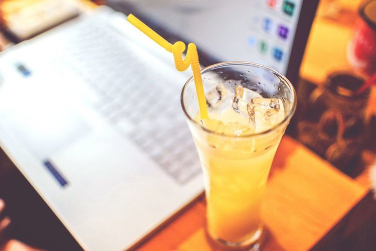 High Angle View Of Drink On Table By Laptop