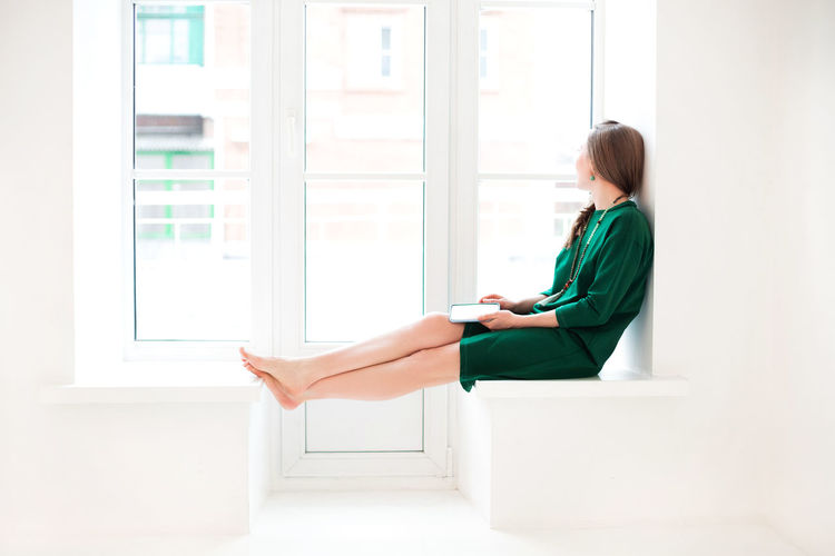 Side view of woman sitting on window