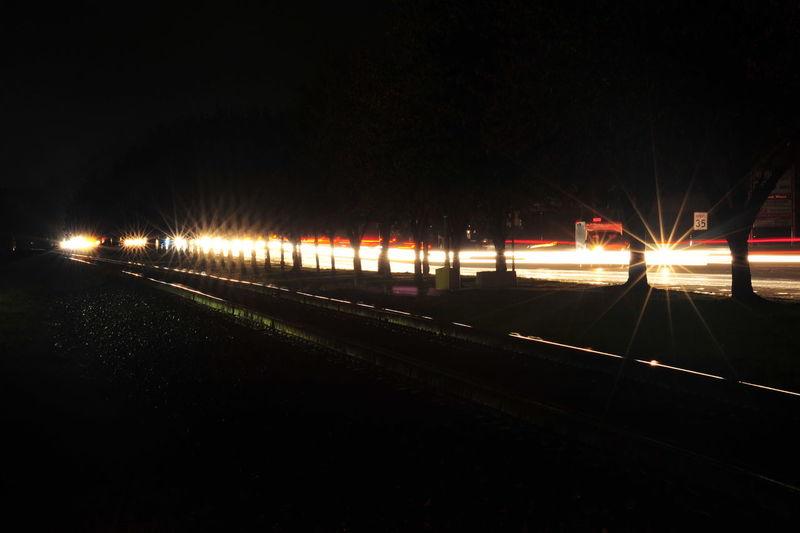 Blurred Motion Horizontal Illuminated Lens Flare Light Trail Long Exposure Motion Night No People Outdoors Sky Speed Star Bursts Transportation Railroad Track