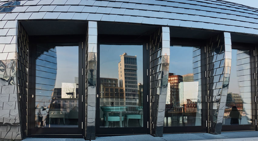 Duesseldorf, Germany - February 27, 2016: Skyline of Duesseldorf Media Harbor reflects nicely in the glass front windows of the modern Chrome Egg building in Duesseldorf Architecture Architecture Blue Sky Building Exterior Built Structure City Day Düsseldorf Landmark M Medienhafen New Media Harbor No People Outdoors Sky Urban Vivid Water