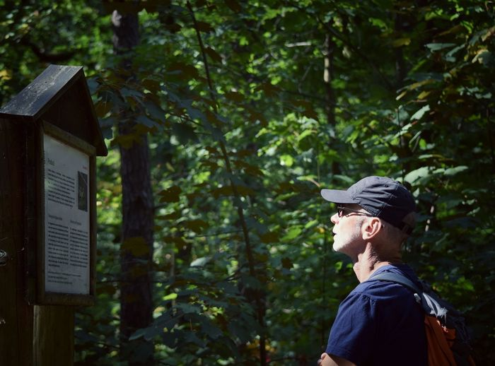 Side view of man wearing cap reading information sign in forest