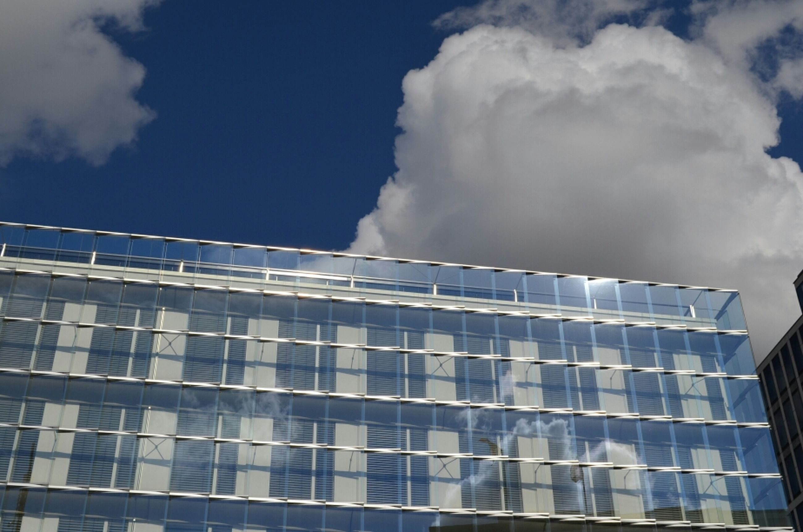 low angle view, architecture, built structure, building exterior, sky, cloud - sky, modern, building, cloudy, cloud, city, office building, blue, glass - material, pattern, day, outdoors, window, no people, reflection