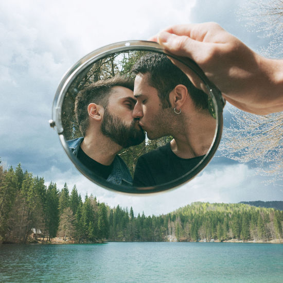 Reflection of gay couple kissing in mirror held by hand over lake against sky