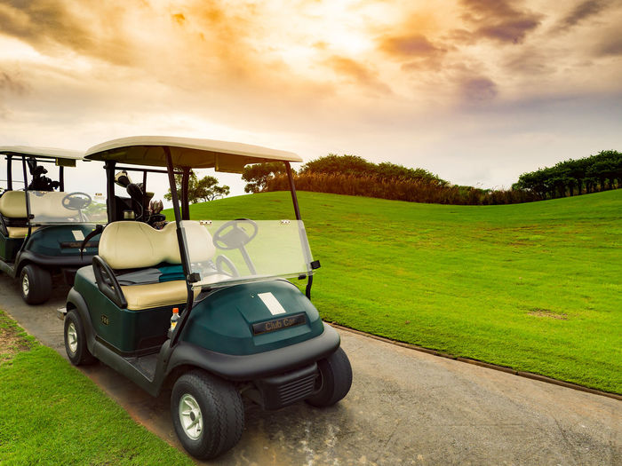 Golf carts or golf club cars on foot path in a green golf course fairway with beautiful sunset or sunrise sky in a sunny day Beauty In Nature Cart Cloud - Sky Day Fairway Field Golf Golf Course Golfer Grass Land Vehicle Landscape Mode Of Transport Nature No People Outdoors Scenics Sky Sunset Transportation Tree First Eyeem Photo EyeEmNewHere