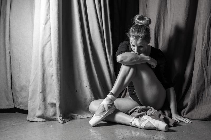 Thoughtful ballerina sitting on floor