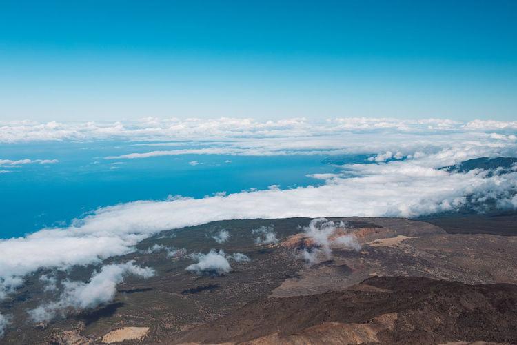 Clouds over volcanic landscape against blue sky