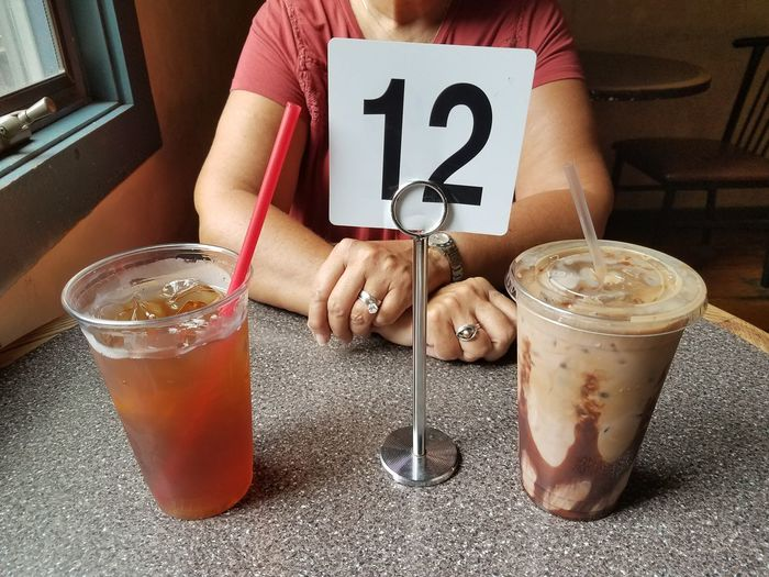 Midsection of woman having drinks with number 12 at table in cafe