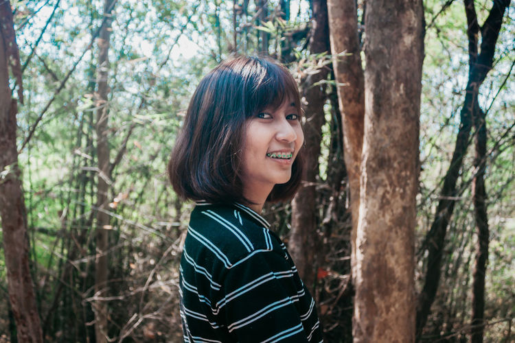 Portrait of smiling young woman by trees in forest