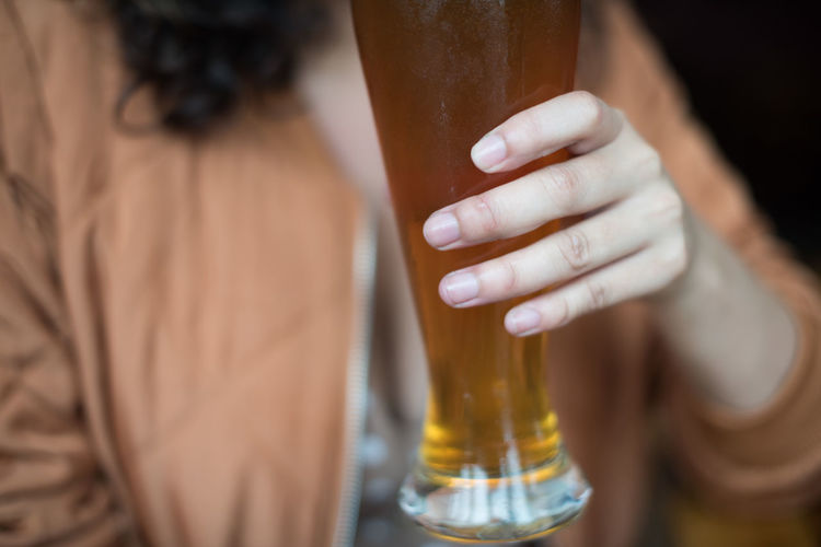 Midsection of woman holding beer glass